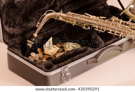 Shiny saxophone lying across open instrumental casing with black velvet interior and pile of money inside - stock photo