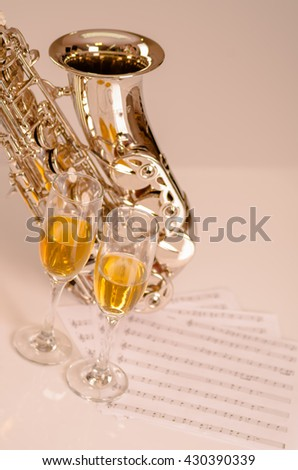 Shiny saxophone lying on white surface, musical notes paper and two glasses of champagne sitting next to it - stock photo