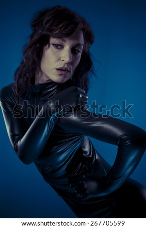 Shiny, sexy brunette in black latex bodysuit tight and wild poses - stock photo