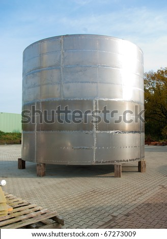 shiny silo stored outside for further processing - stock photo