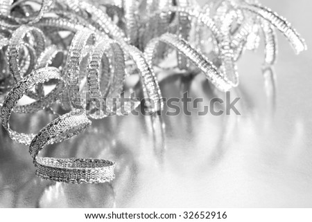 Shiny silver curling ribbon on reflective wrapping paper.  High key black and white macro with extremely shallow dof.  Copy space included. - stock photo