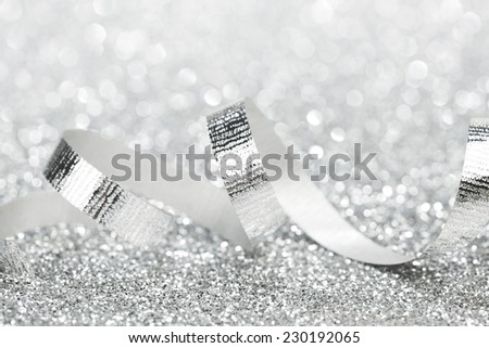 Shiny silver gift ribbon on bokeh background close-up - stock photo