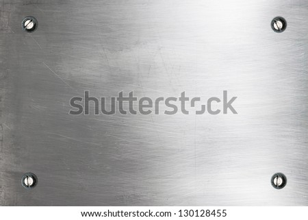 Shiny silver metallic plate with bolts - stock photo