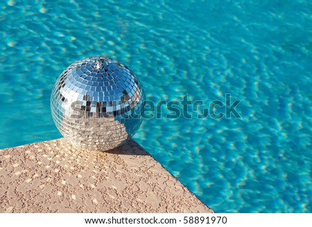 Shiny silver party disco ball beside swimming pool - stock photo