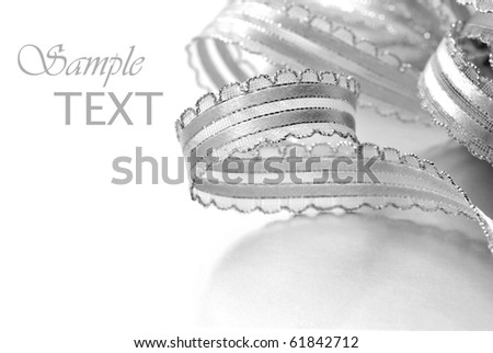 Shiny silver ribbon curls on silver box with copy space.  Macro with extremely shallow dof. - stock photo