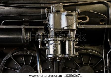 Shiny silver steam engine parts with black background suitable for steampunk theme.