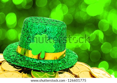 Shiny St Patrick's Day hat and gold coins on green twinkling background - stock photo