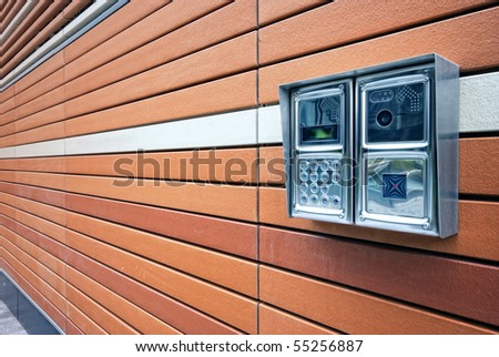 Shiny stainless steel intercom at a modern apartment block. - stock photo