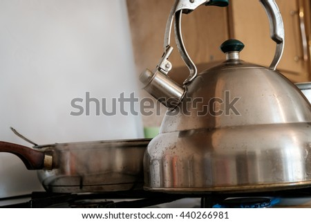 Shiny stainless steel kettle sitting on gas stove with steam coming from the spout - stock photo