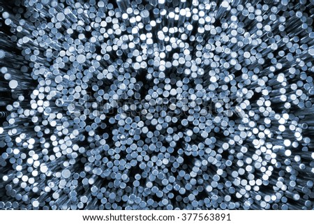 Shiny steel round bars. Blue tinted industrial background - stock photo