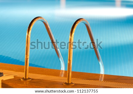 Shiny steel swimming pool ladder view at night - stock photo