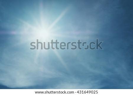 Shiny sun lens flare on blue sky - stock photo