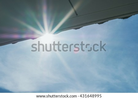 Shiny sun lens flare with roof on blue sky - stock photo