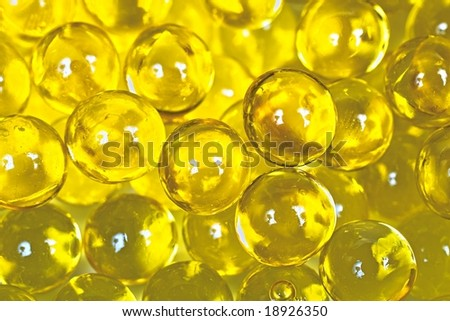 Shiny yellow capsules with fish oil - stock photo