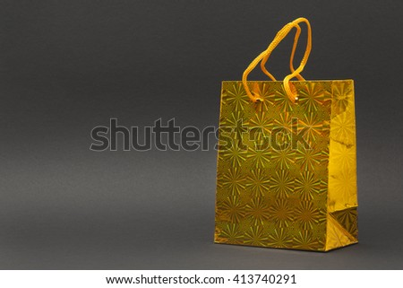 Shiny yellow gift bag isolated on a black background - stock photo