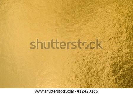 Shiny yellow gold golden paper foil leaf decorative texture background: Bright brilliant festive glossy metallic look textured backdrop:  Metal steel material pattern surface for design decoration - stock photo