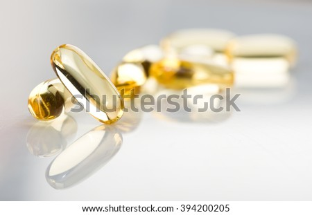 shiny yellow vitamin e fish oil capsule on white background  - stock photo