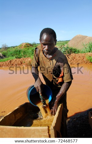 SHINYANGA, TANZANIA-MARCH 18: An unidentified miner looks for gold March 18, 2010in Shinyanga, Tanzania. Tanzania is the third gold producer in Africa after Ghana and South Africa. - stock photo