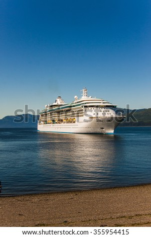 Ship anchored at the beach in a bay of Alaska on a clear blue sky. - stock photo
