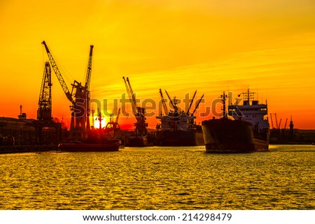Ship and cranes at sunset in port of Gdansk, Poland. - stock photo