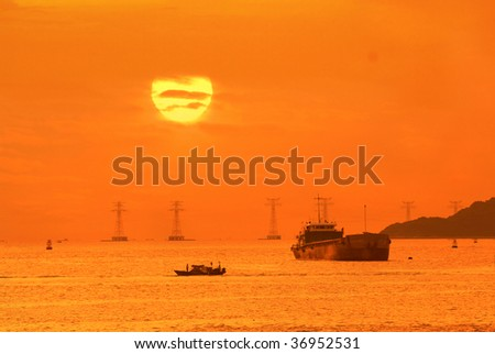ship and electric pillar over blue sky in sunset - stock photo