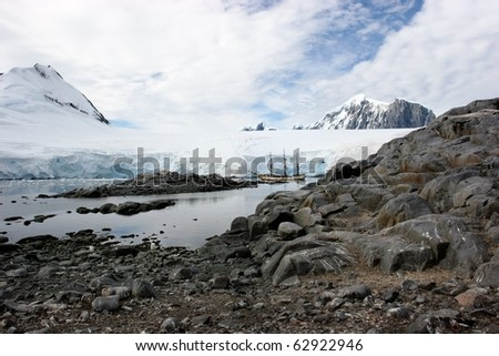 ship and penguins at Port Lockroy, Antarctica - stock photo