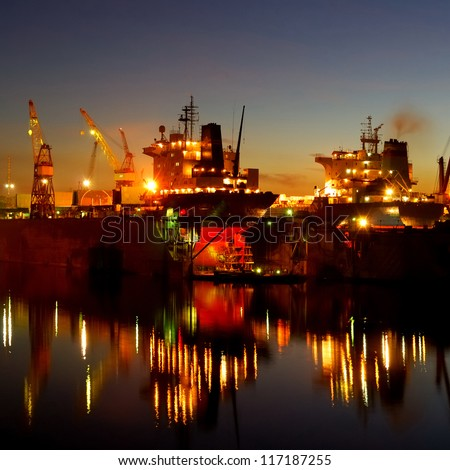 ship are being fixed and painted at the shipyard docks by night - stock photo