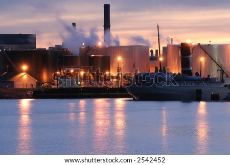 Ship docked by industrial buildings at sunset - stock photo