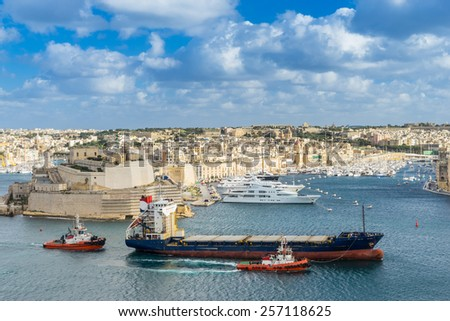 Ship entering the Grand Harbor going to the Three Cities of Cospicua, Vittoriosa and Senglea in Valletta Malta - stock photo