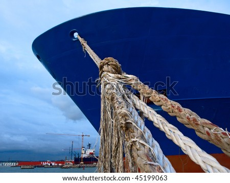 ship fixed with ropes in the harbor - stock photo