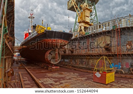 Ship for repairs in large floating dry dock.