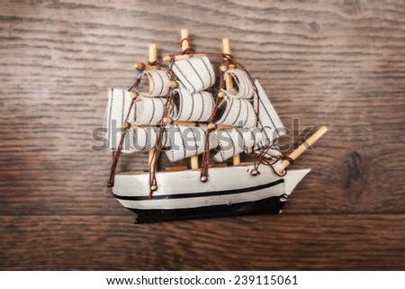ship frigate parquet linoleum brown pirate line figurine wooden brown background - stock photo