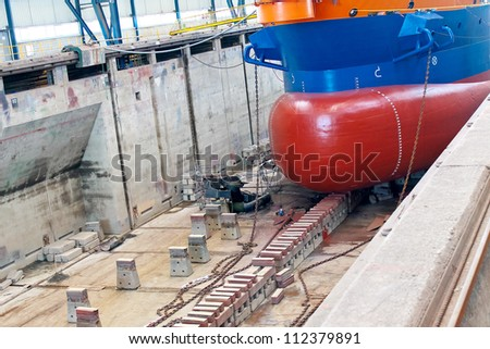 Ship in  shipyard's covered dry dock - stock photo