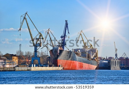 Ship in the dock with elevating cranes - stock photo