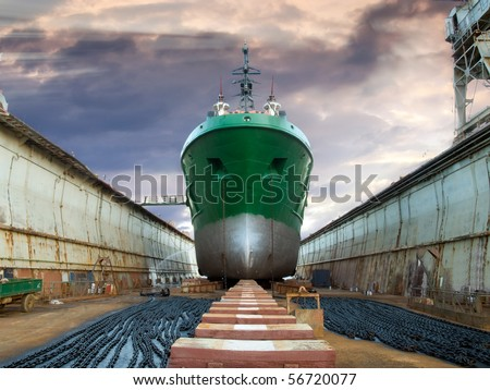 Ship in the dry dock during the overhaul, under  dramatic sky. - stock photo