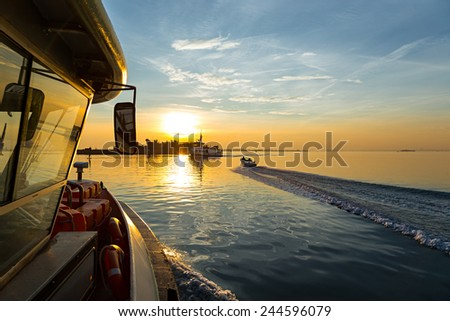 ship in the ocean at sunset - stock photo