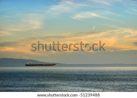 Ship in twilight on the ocean with new moon in background. - stock photo