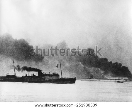 Ship leaving Dunkirk carrying defeated British and French soldiers to England. In the background the French port of Dunkirk burns under the German advance. World War 2. May 26-June 4, 1940. - stock photo