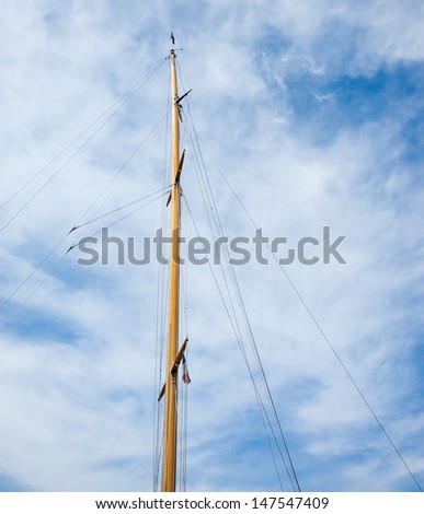 Ship mast with french flag and blue sky with white clouds on background.