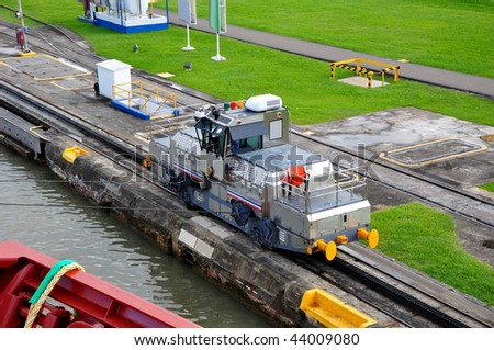 ship passes through a sluice in the Panamanian channel.Panamanian train leads ship through channel. - stock photo