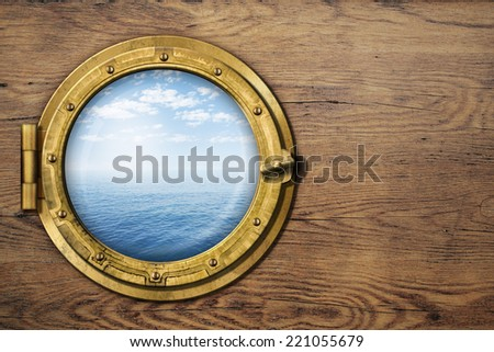 ship porthole on wooden wall - stock photo