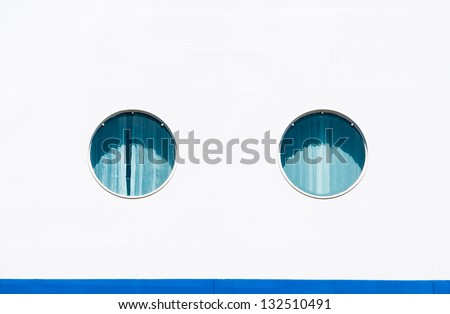 Ship porthole windows on white ocean cruise liner. Two portholes at the passenger travel vessel. - stock photo