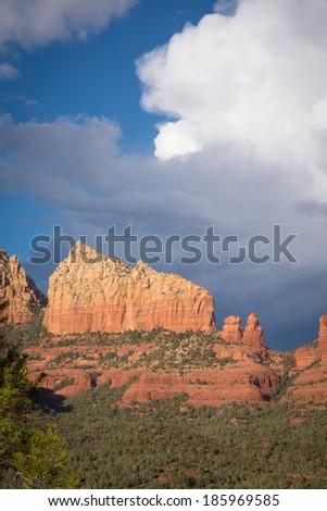 Ship Rock, a landmark sandstone cliff in Sedona, Arizona, on a cloudy afternoon. Vertical orientation.