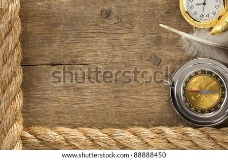 ship ropes and compass with feather at old wooden background