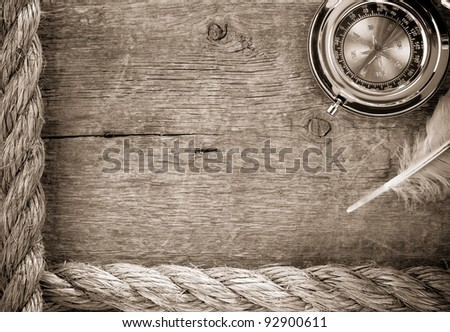 ship ropes and compass with feather on old wooden background