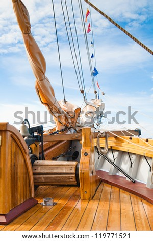 ship's Bell and anchor lifting mechanism on an old sailboat - stock photo