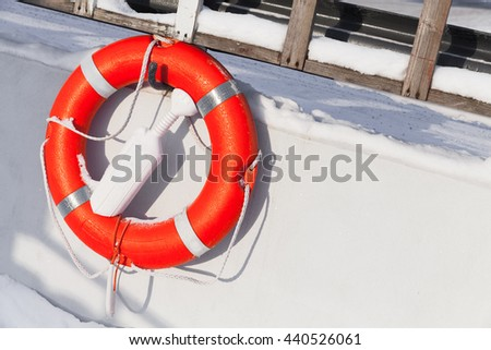 Ship safety equipment, orange lifebuoy on white boat in winter - stock photo