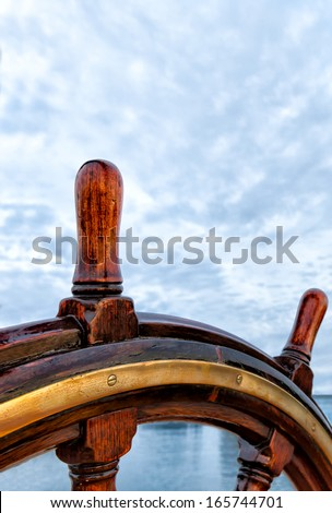 Ship wheel made of wood and brass. Close up detail on a sailboat at sea. Copy space. Concept for leadership, responsibility, steering, leading, guiding, in charge  - stock photo