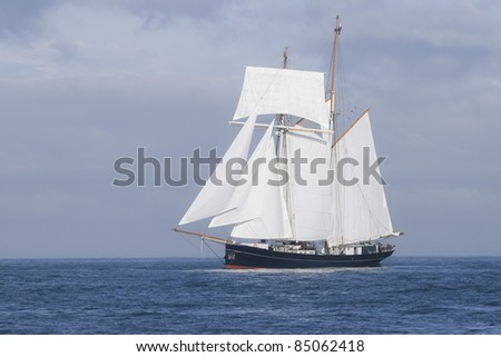 Ship with white sails in the calm sea - stock photo