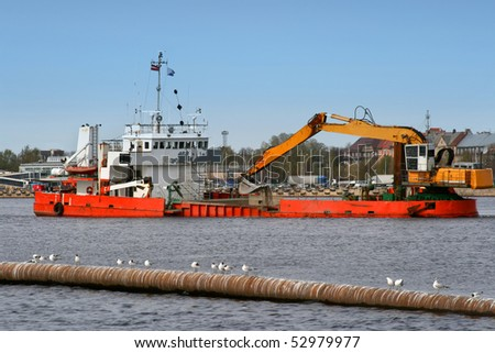 Ship with working excavator on board. Heavy machine is dredging the river of Daugava in center of port in Riga, Latvia. - stock photo